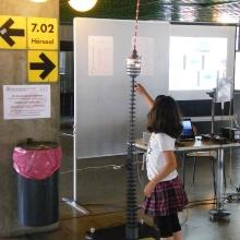 Schwingungsmodell des Stuttgarter Fernsehturms mit interessierter Besucherin am  Tag der Wissenschaft 2012