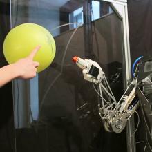 Roboter Ataro 720 spielt Ball Der Roboter Ataro 720, der hinsichtlich der Funktionsweise einem menschlichen Arm nachgebaut wurde, spielt einen gelben Ball zurück.